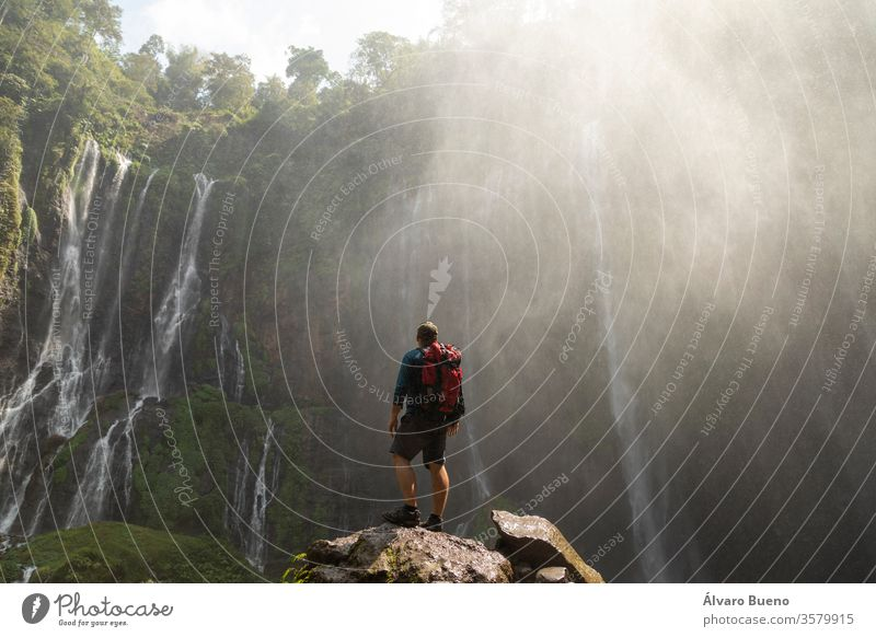 A backpacking adventurer gazes in awe at the massive rock circus formed by the intense waterfalls at Tumpak Sewu in East Java, Indonesia. forest active mountain