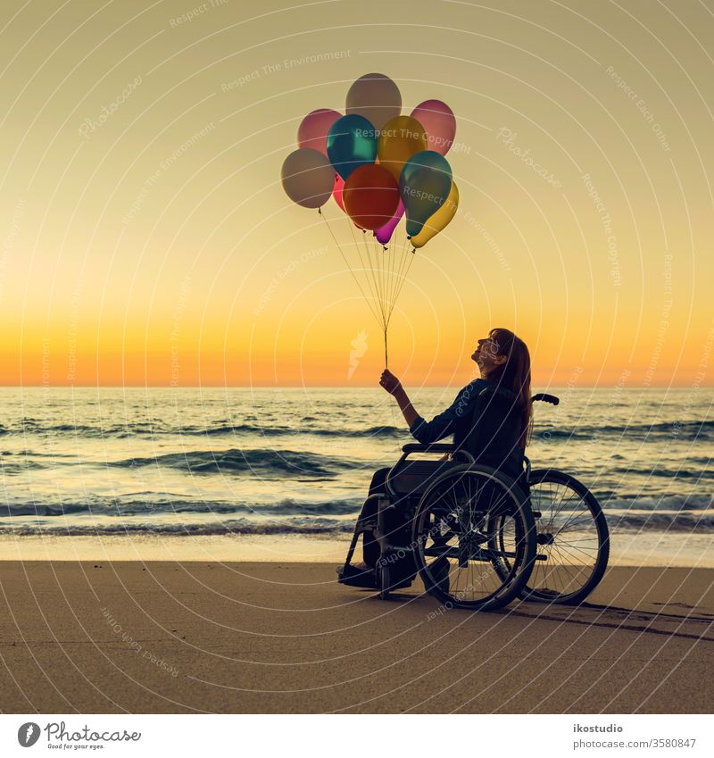 Anything is possible woman wheelchair happy beach balloons sunset handicapped healthcare joy leisure success motivation activity disability relaxing sand sea