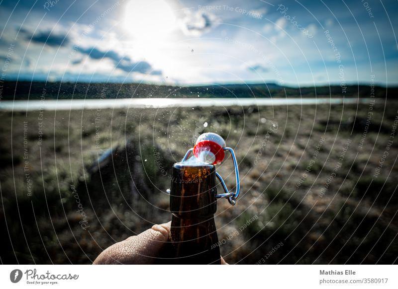 Enjoy life. Cheers! bottle Neck of a bottle Bottle of beer Beer swing stopper office Sun Back-light Lake Drinking Beverage Glassbottle by hand open Beer garden