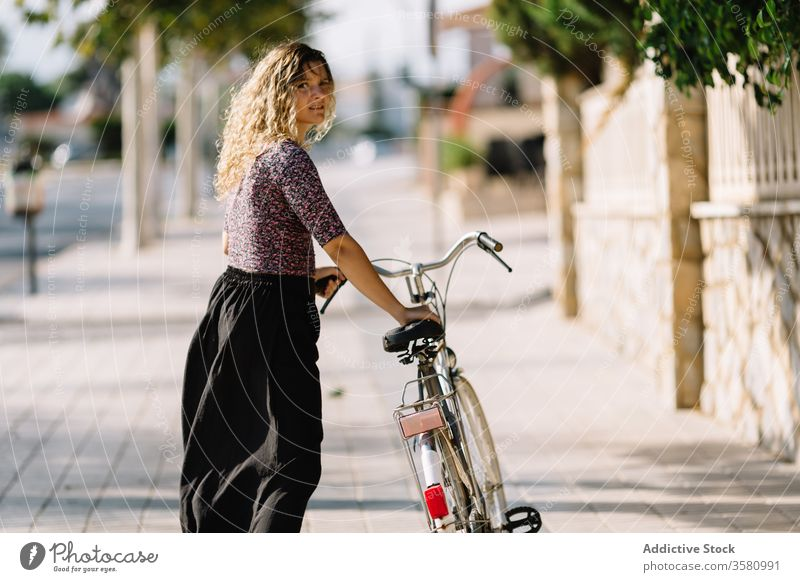 Tranquil woman with bicycle in park bike summer weekend enjoy walk cyclist calm female sunny tranquil serene outfit daytime rest green tree lady carefree