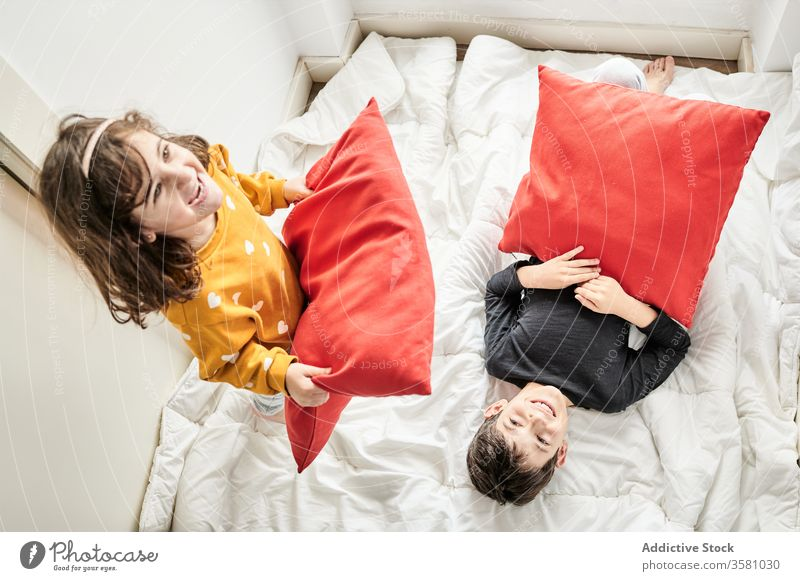 Playful siblings having pillow fight on bed home fun children blanket playful brother lounge sister having fun cozy soft together friendly childhood joy bedroom