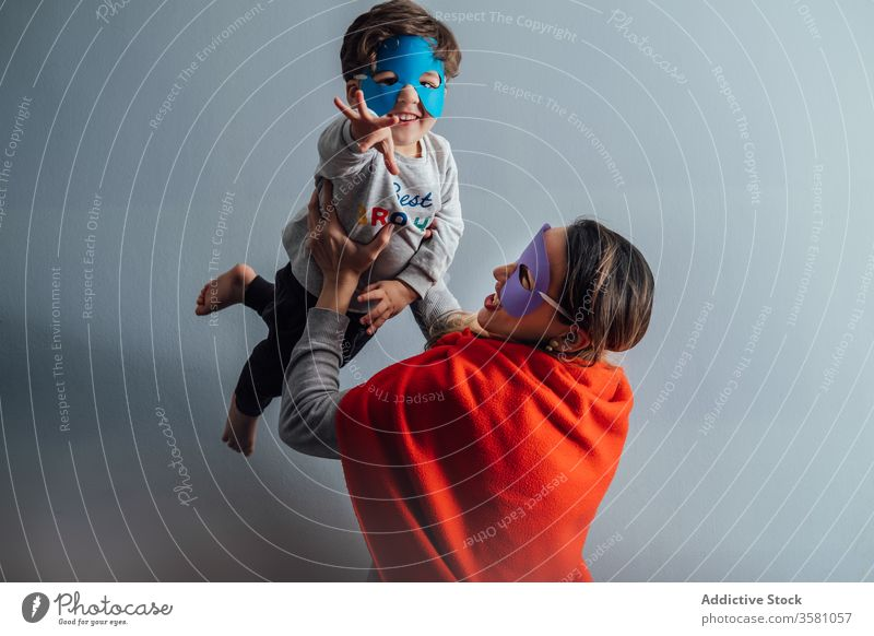 Smiling mother playing with son at home superhero toss mask game having fun boy together pretend creative playful cheerful little weekend kid child happy