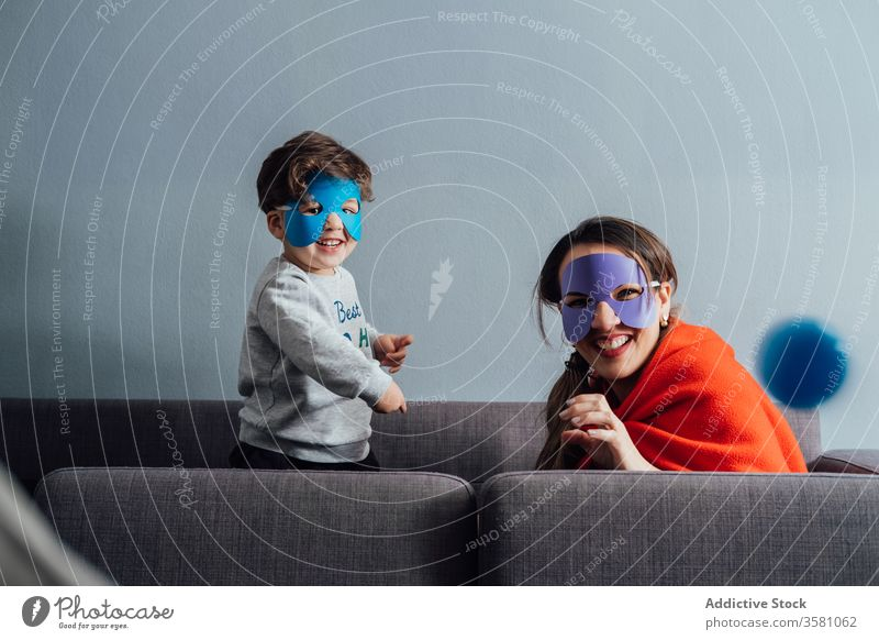 Creative mother and son in superhero masks at home play game creative pretend having fun playful cheerful little weekend boy kid child happy childhood joy