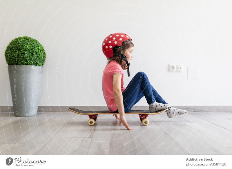 Happy preteen girl riding skateboard at home game entertain fun child play decor longboard helmet kid dream stay at home having fun safety social distancing