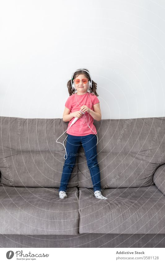 Happy preteen girl in headphones with mic singing while playing alone at home microphone having fun child sofa singer superstar happy music kid dance carefree