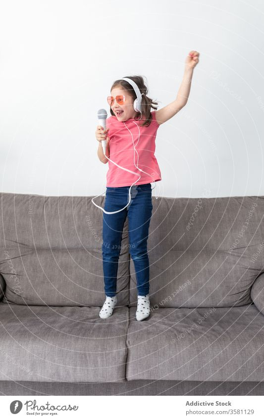 Happy preteen girl in headphones with mic singing while playing alone at home microphone having fun child jump sofa singer superstar happy music kid dance