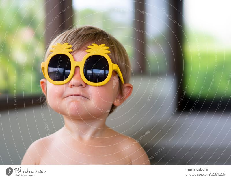 Little boy wearing yellow pineapple sunglasses on back porch toddler wearing sunglasses happy sunny home house outdoor florida youth young child caucasian funny