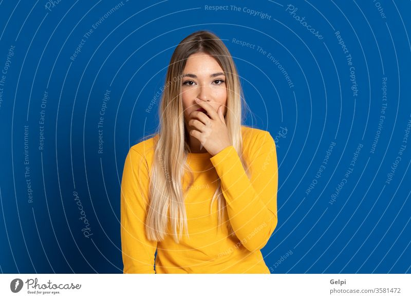 Blonde girl wearing a yellow T-shirt person blue blonde scaredy-cat scary intimidate mute mouth cover fair hair head expression gesture young beautiful female