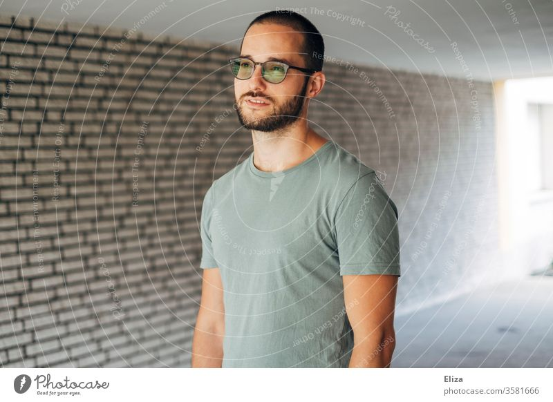 A man in a T-shirt stands in an underpass and looks thoughtfully into the distance. Vision. vision Meditative Man Bright Underpass visionary Wall (building)