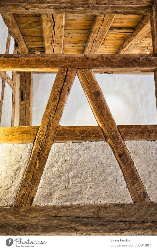 "Wooden beams in the interior of a building. Wooden beam construction in ""A"" shape wooden beams studding Wooden ceiling Blanket Old building refurbishment"