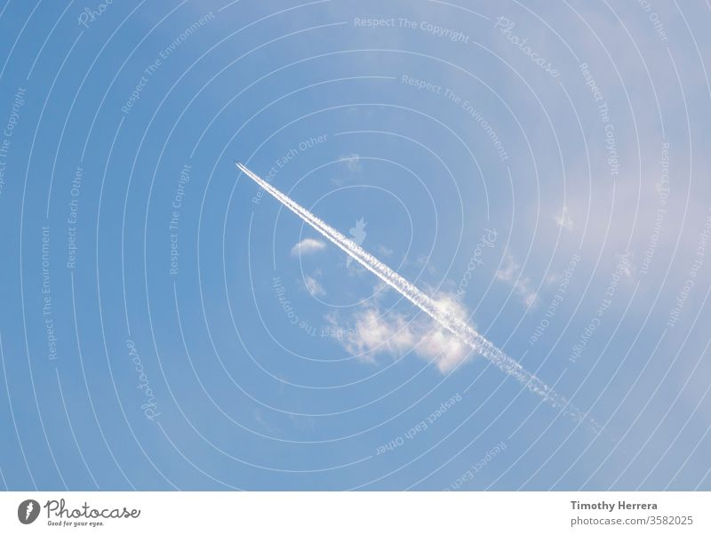 An airplane leaving behind a condensation trail or contrail. sky blue sky travel sky trail vapor trail clouds flying vacation travel leisure freedom