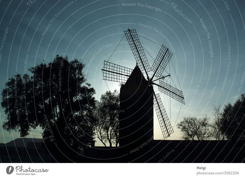Silhouette of a mill for water production on Mallorca in the evening light Mill Windmill Sky Light Shadow Contrast tree shrub Back-light Old Historic