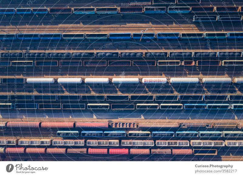 Aerial view of colorful freight trains on the railway station. Wagons with goods on railroad. Heavy industry. Industrial conceptual scene with trains. Top view. Photo captured with drone.