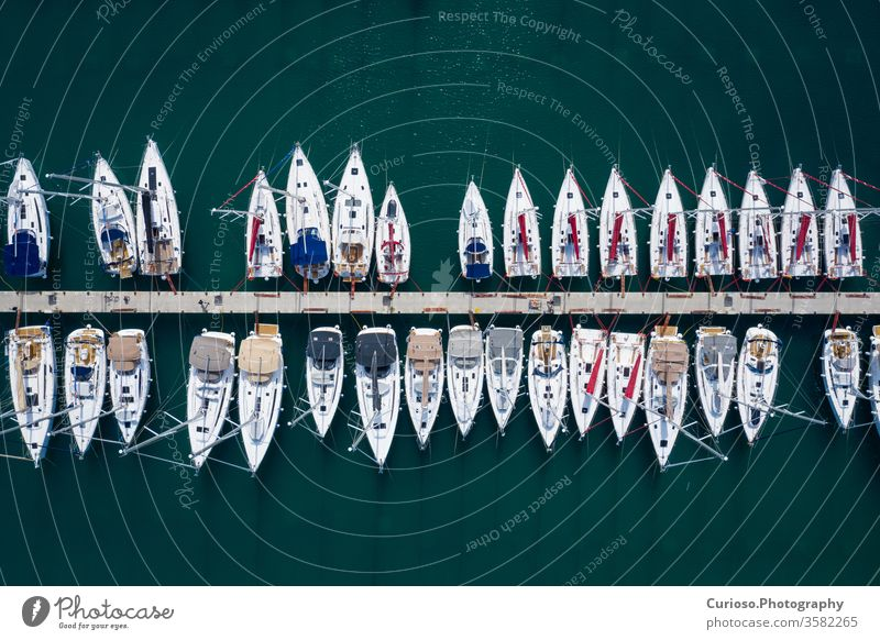 Aerial view of a lot of white boats and yachts moored in marina. Photo made by drone from above. aerial harbor pier sea dock water port luxury summer blue