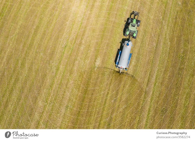 Aerial view of farming tractor plowing and spraying on field.  Agriculture. View from above. Photo captured with drone. aerial machine agriculture harvester