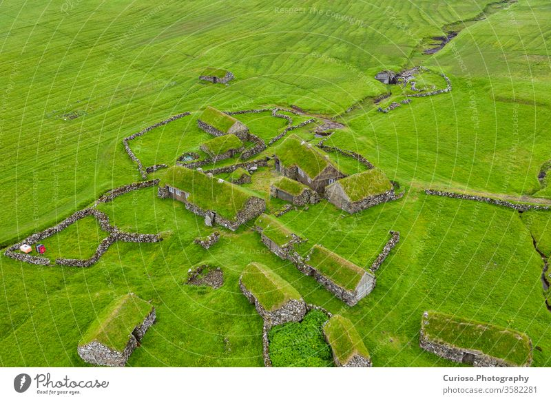 Aerial view of fishing village in Koltur island. Faroe Islands. Green roof houses. Photo made by drone from above. Nordic natural landscape. sea wooden koltur