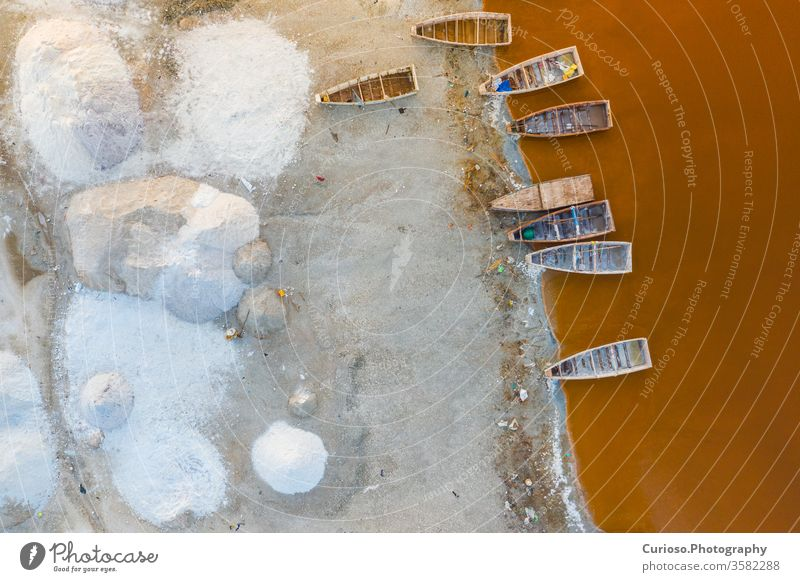 Aerial view of the small boats for salt collecting at pink Lake Retba or Lac Rose in Senegal. Photo made by drone from above. Africa Natural Landscape. senegal