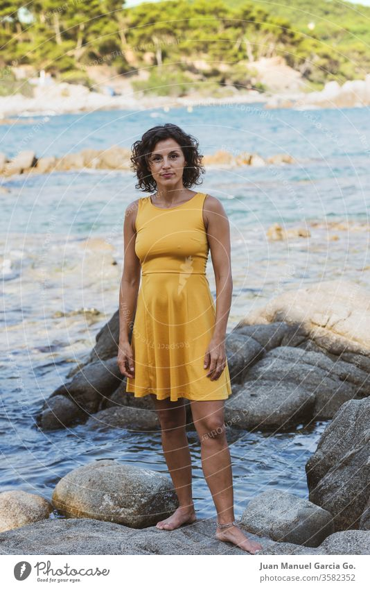 A beautiful female Latina wearing a yellow dress standing on a rock on the seashore woman girl beauty young pretty attractive people adult white natural person