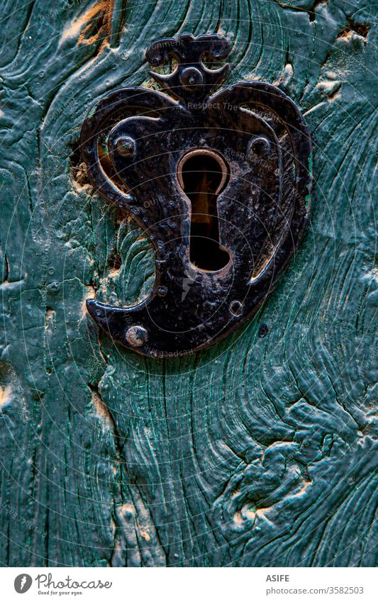 Old heart shaped door lock on a blue wooden door detail close up old rustic iron wrought painted front rural closed black ancient antique architecture vintage
