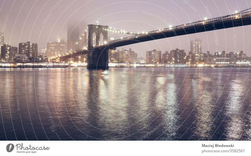 Brooklyn Bridge at a foggy night, New York City, USA. new york brooklyn bridge city manhattan skyline water reflection usa urban famous nyc panorama filtered