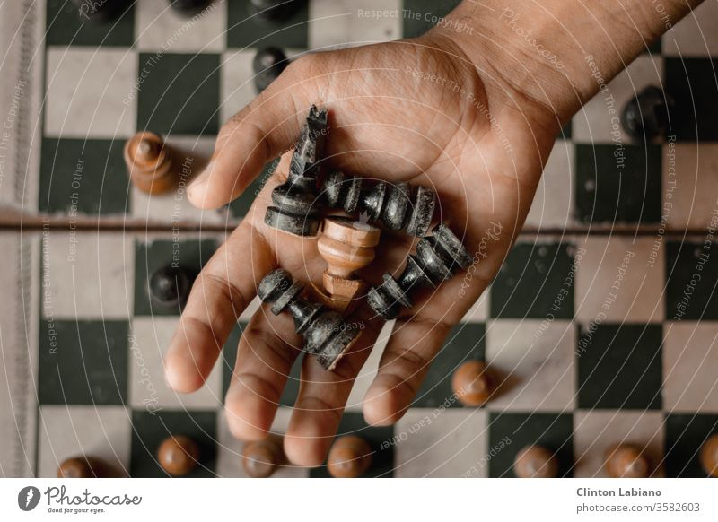 a hand holding five chess pieces Black White Hand Chessboard Chess piece Brown Move (board game) Grasp Square Wood grain Classic Brainteaser Rustic Wooden board