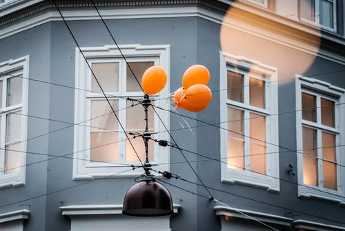 A group of balloons are attached to an overhead line Balloon Movement To hold on Fixed Facade House (Residential Structure) house wall cross Wall (building)
