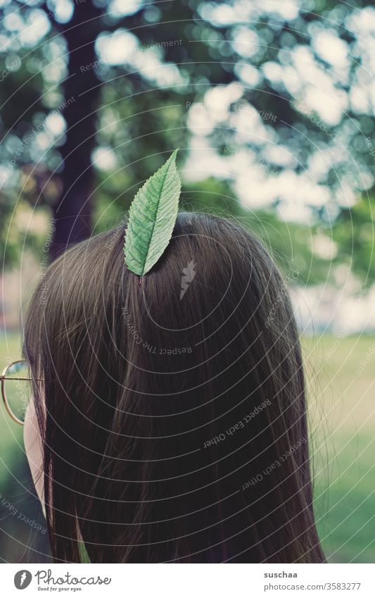 city indian | girl wears a leaf, instead of a feather, in her hair Youth (Young adults) teenager Head Hair and hairstyles brunette fine hair Back of the head