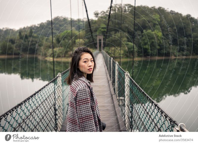 Calm Asian female traveler standing on suspension bridge over river tourist forest adventure tourism vacation picturesque peaceful journey serene reflection