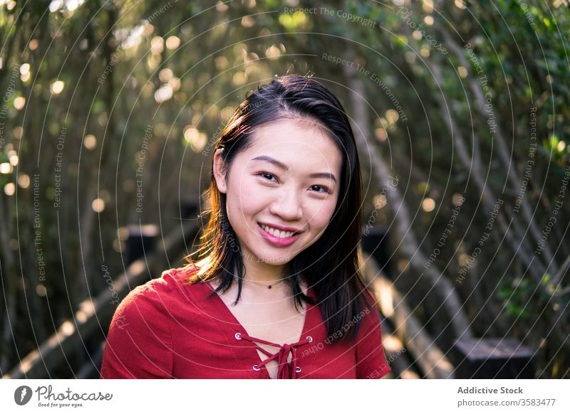 Dreamy young Asian woman standing in park contemplate calm dreamy feminine mouth opened human face necklace quiet think serene summer youth peaceful tree