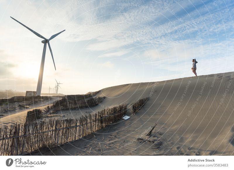 Unrecognizable traveler standing on sand hill near windmill at sunset sky horizon harmony landscape scenic hillside explore skyline calm cloudy sundown serene