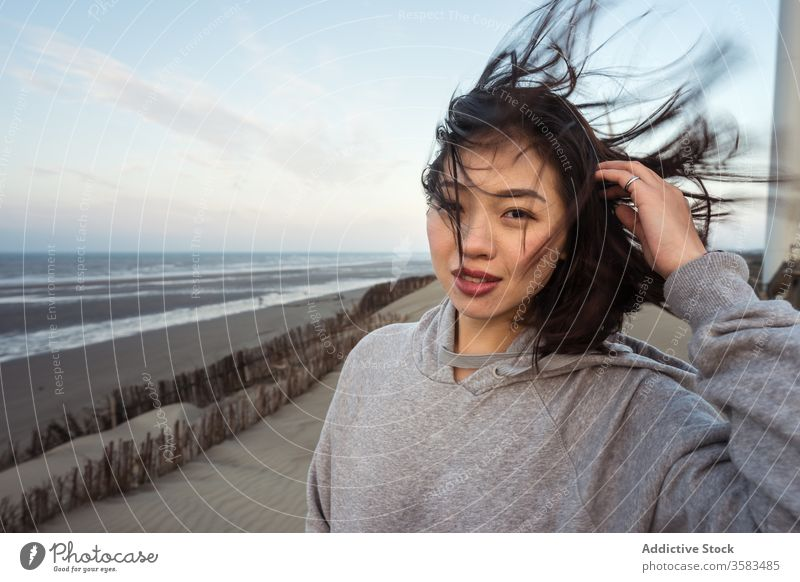 Young Asian woman standing on sea beach on windy weather skyline harmony sand touch hair coast thoughtful reflective calm coastline weekend recreation wistful