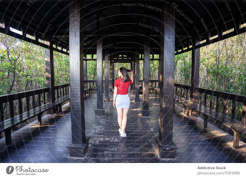 Asian female standing on wooden veranda in forest in daylight woman bench column architecture touch hair old free time recreation antique serene fence floor