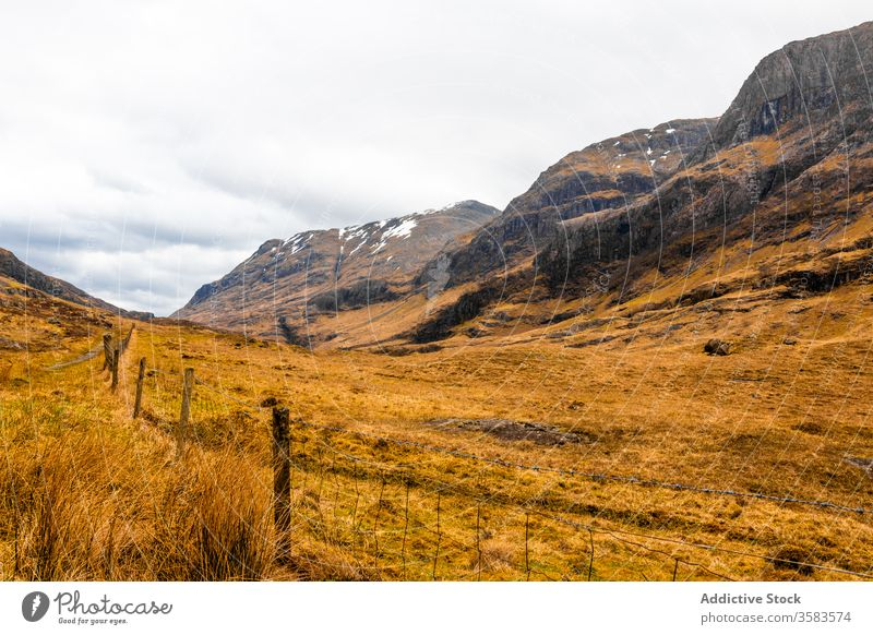 Remote road in endless mountainous valley highland rock nature landscape countryside route ridge range terrain scotland glen coe sky cloudy grass spring travel