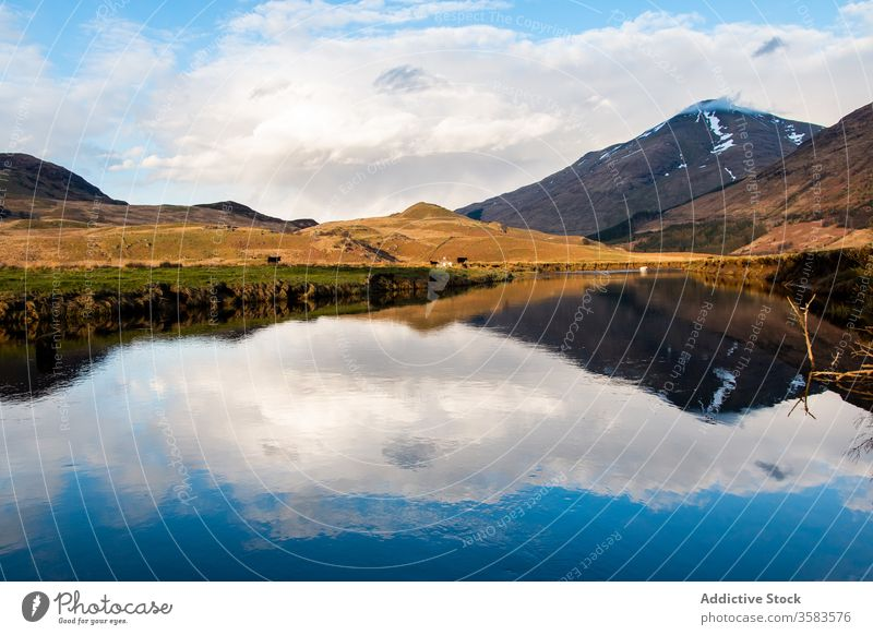 Cloudy sky and mountain reflected in lake reflection landscape calm peak nature scotland highland glen coe water scenery scenic environment peaceful wild serene