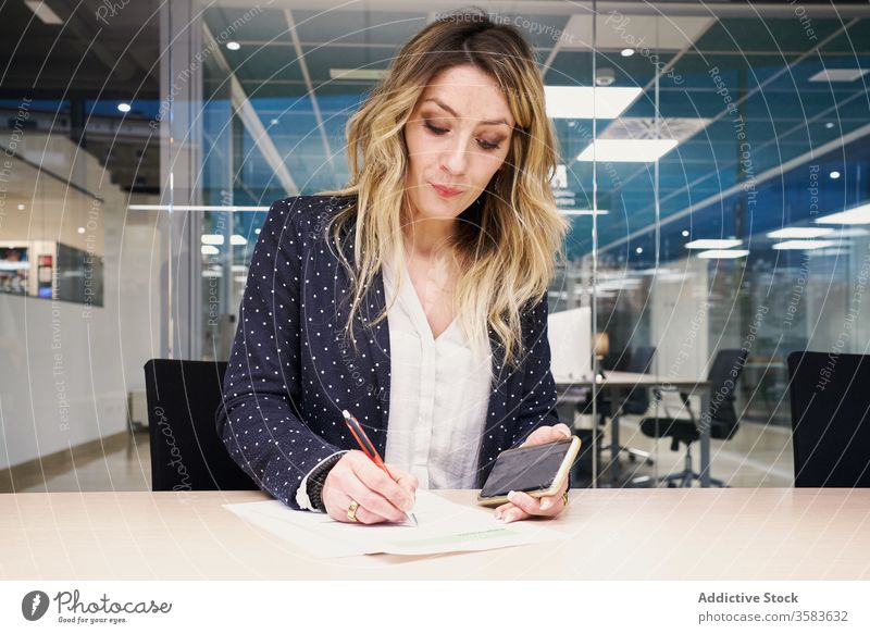 Modern busy woman with smartphone making notes in document work workspace take note young entrepreneur businesswoman write serious female paper gadget modern