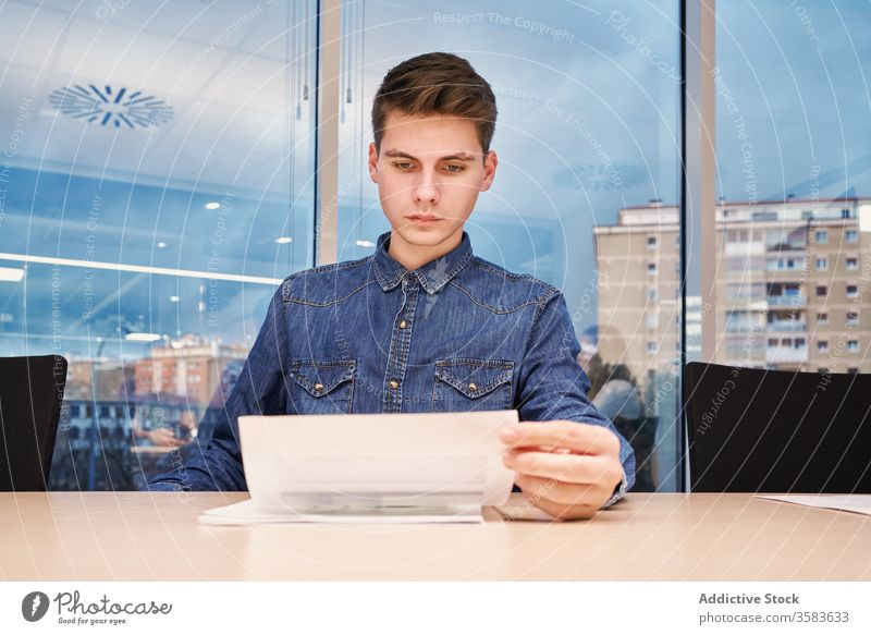 Busy male employee doing paperwork in office document job man worker read busy serious shirt table casual sit workplace modern professional open space