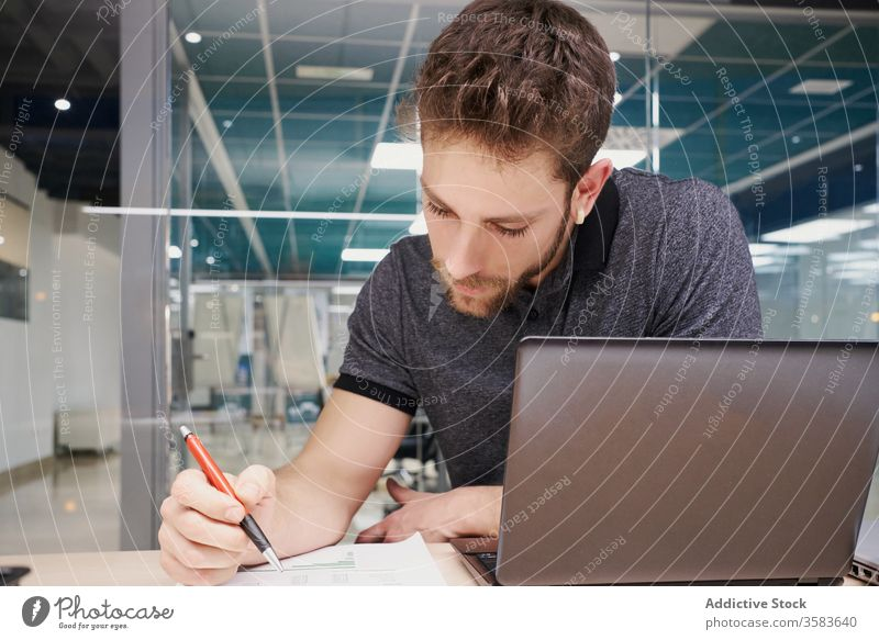 Concentrated male entrepreneur reading documents in office paperwork analyze businessman laptop focus report table sit concentrate job professional serious busy