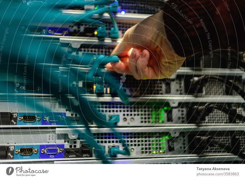 Man data center technician performing server maintenance infrastructure engineer rack cables replacing blade mounted fiber optics rj45 recovery man working it