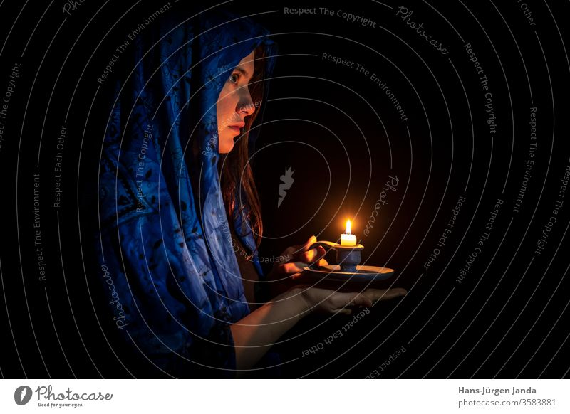 Sad young woman with candle and blue headscarf Face sad black portrait frontal profile serious art gloomy candlestick hands flame burn light scary look eyes