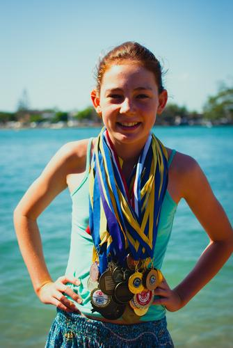 My champion. // A girl is standing happily at the edge of the river, laughing. She has many medals hanging around her neck. She has waved her arms. Girl