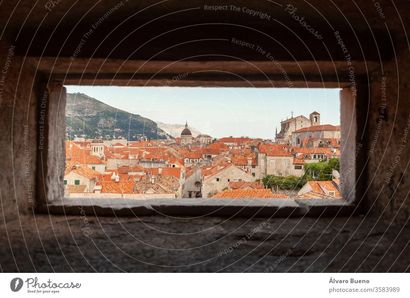 Orange roofs of Dubrovnik, seen from the wall, through a small window, under the shadows of afternoon clouds, on the banks of the Adriatic Sea. adriatic sea