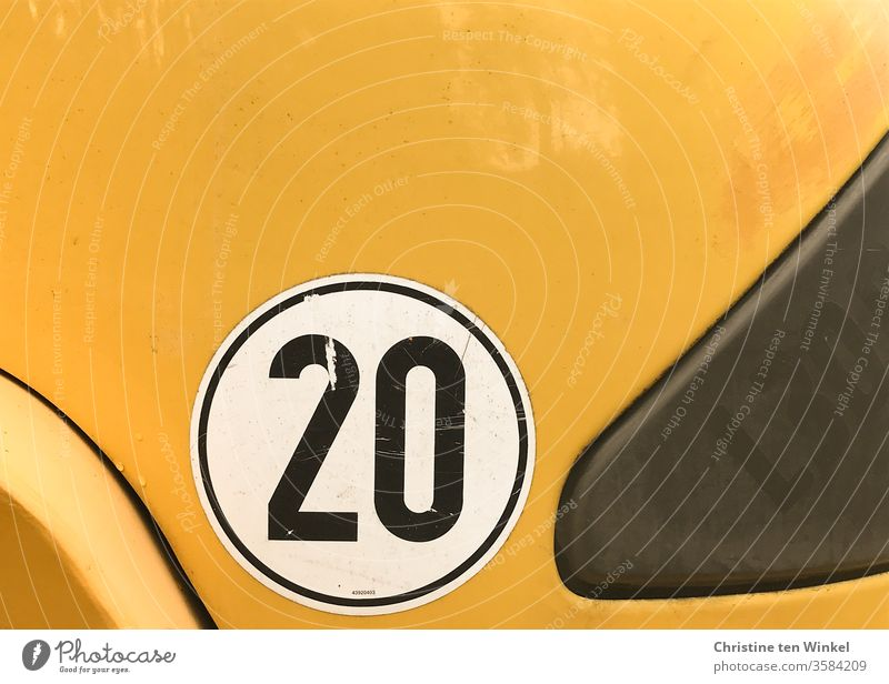 black 20 on white and yellow twenty Label Digits and numbers digit Black White Yellow yellow background Utility vehicle Sign Vehicle Signs and labeling