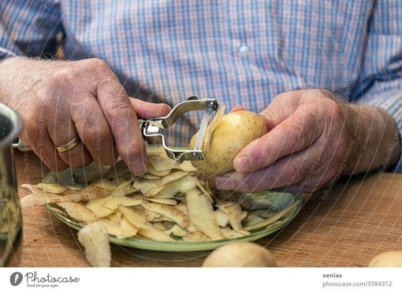 Senior in blue check shirt peels potatoes at the table hands Senior citizen senior citizens Potatoes Peeling knife Plate Wedding band Checkered Shirt Man Food