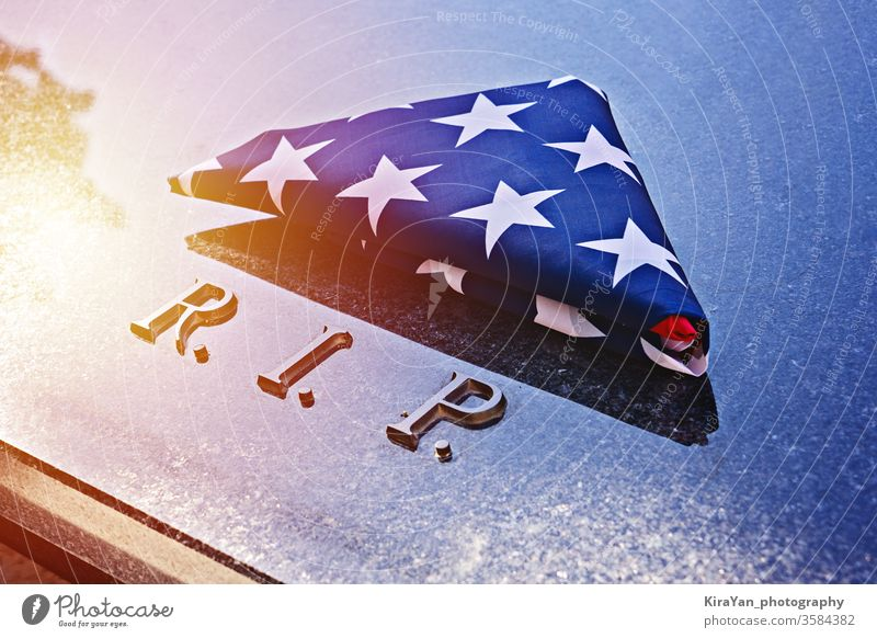 Folded into triangle American flag on memorial marble tomb with R.I.P. text american flag grunge us 4th july banner usa concept memorial day symbol patriotism