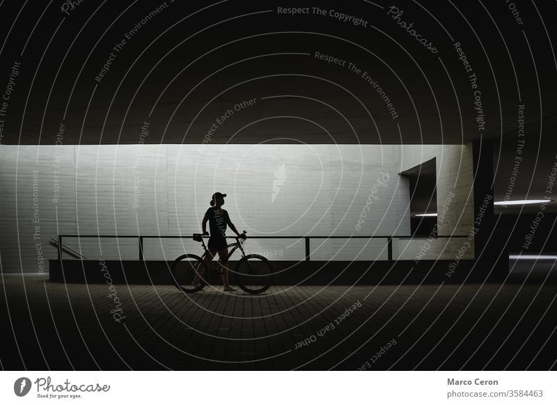 silhouette of a person pushing his bike through the streets of the city one person built strucuture contrast architecture city street side view young woman