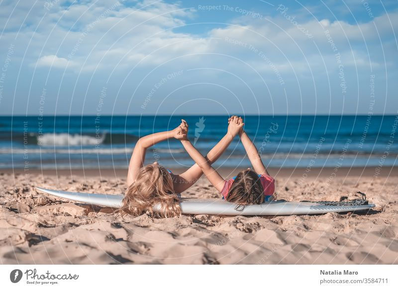 Two little girls' hands holding together laying on a surfboard on the sandy ocean beach. Love, friendship, togetherness concept. kid young child people love two