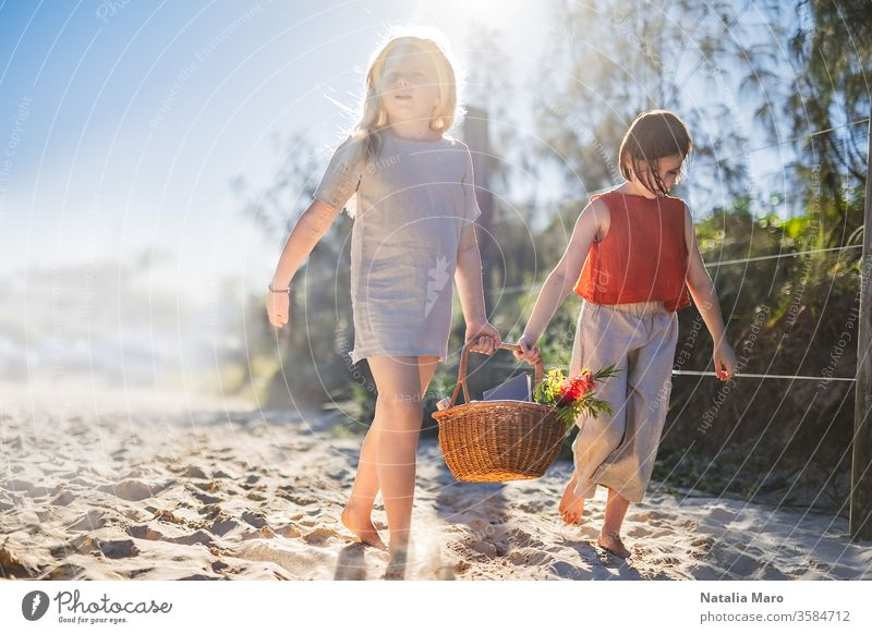 Little girls walking barefoot on the sand and caring a picnic basket together. Summer leisure, love and friendship. nature park child activity summer recreation