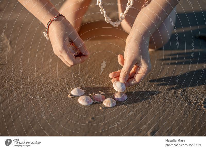 Little girl's hands creating a heart from seashells on the ocean sandy beach. child kid love seashore summer sun outdoor nature lifestyle toddler travel