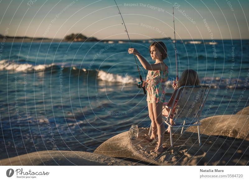 Two little girls are fishing in ocean surf at sunset. Summer leisure, hobby and fun for kids. people vacation person young recreation water caucasian family