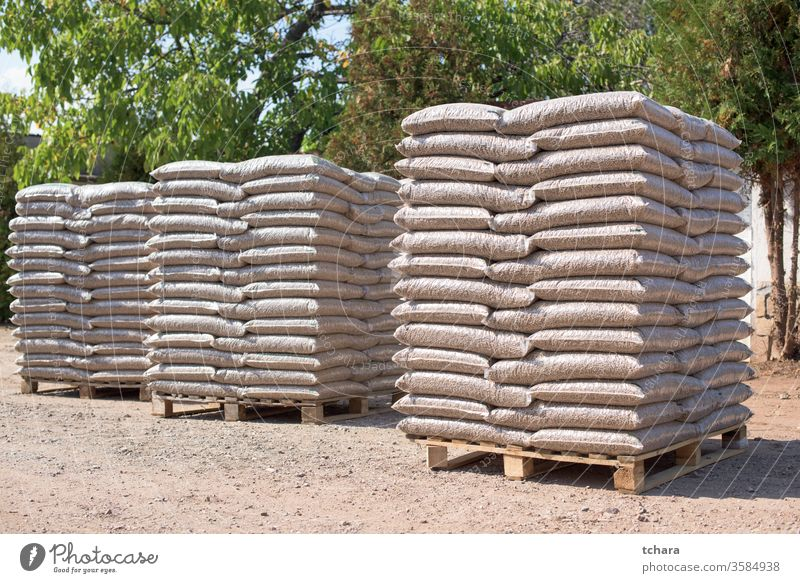 Many sacks that are filled with pellets placed on pallets reserves environmentally storage resources green friendly bags coniferous alternative product domestic